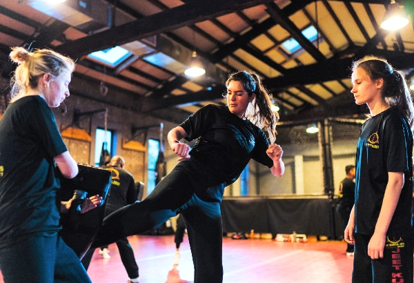 Two kickboxers train with the striker sending a low kick into the training pad at shin level.