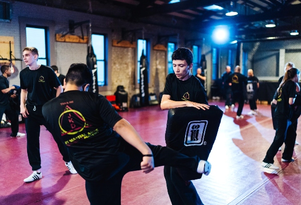 A kickboxer strikes a pad held by a fellow martial arts student.