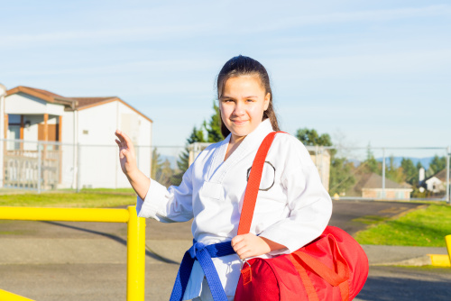 A young girl in a martial arts gi stands in front of a school fence.