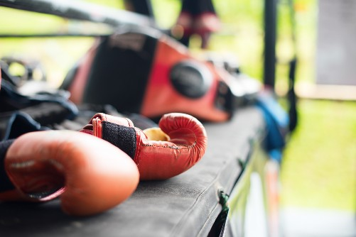 Gloves are left on a mat in the open air of a martial arts summer camp.